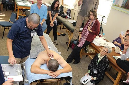 acupuncture doctor teaching a classroom of students