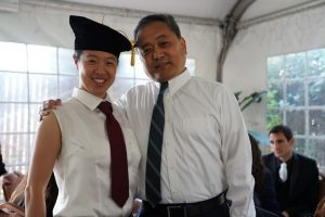 asian woman smiling with older asian man at graduation event