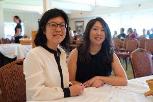 two older asian women smiling at camera at a graduation