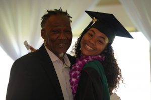 graduate hugging her dad while they smile at camera