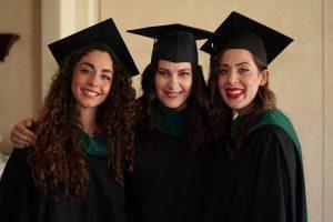 three female graduates smiling at the camera