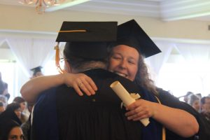 graduate hugging teacher while accepting diploma