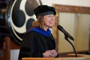woman at pulpit smiling during graduation