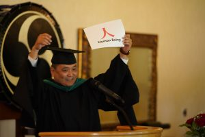 """man at pulpit during graduation holding up a sign that says """"human being"""""""