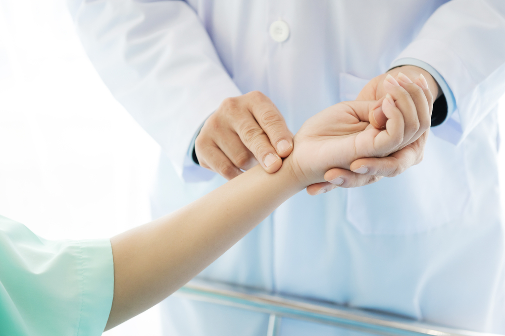 doctor taking patient's pulse at wrist