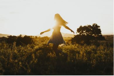 woman dancing in a field at sunset